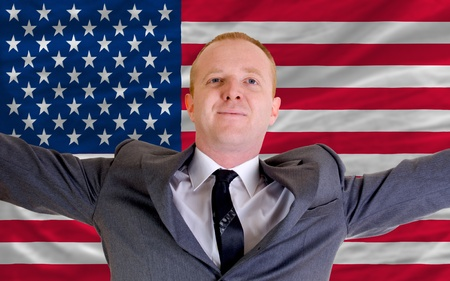 joyful investor spreading arms after good business investment in america, in front of flag photo