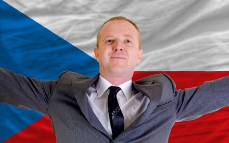 joyful investor spreading arms after good business investment in czech, in front of flag photo