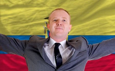 spreading arms: joyful investor spreading arms after good business investment in ecuador, in front of flag Stock Photo