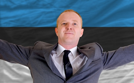 spreading arms: joyful investor spreading arms after good business investment in estonia, in front of flag