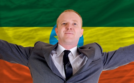 spreading arms: joyful investor spreading arms after good business investment in ethiopia, in front of flag