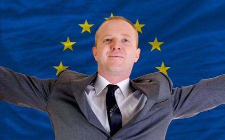 joyful investor spreading arms after good business investment in europe, in front of flag photo
