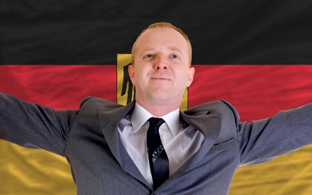 joyful investor spreading arms after good business investment in germany, in front of flag photo