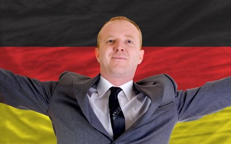 spreading arms: joyful investor spreading arms after good business investment in germany, in front of flag