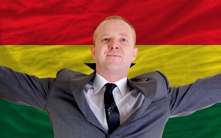 spreading arms: joyful investor spreading arms after good business investment in ghana, in front of flag Stock Photo