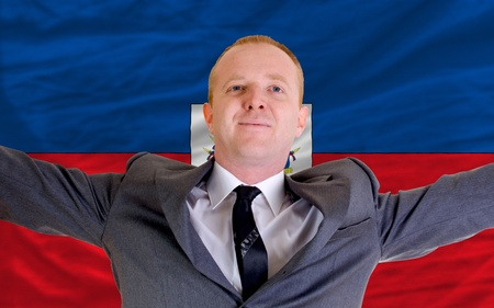 spreading arms: joyful investor spreading arms after good business investment in haiti, in front of flag Stock Photo