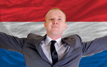 spreading arms: joyful investor spreading arms after good business investment in holland, in front of flag Stock Photo