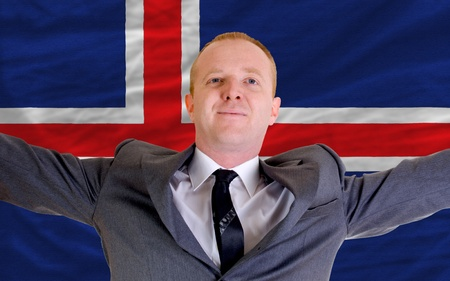 spreading arms: joyful investor spreading arms after good business investment in iceland, in front of flag Stock Photo