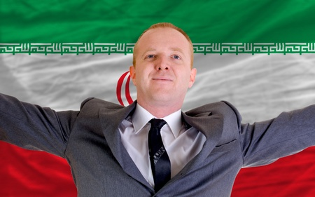 spreading arms: joyful investor spreading arms after good business investment in iran, in front of flag