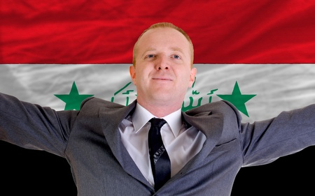 iraqi: joyful investor spreading arms after good business investment in iraq, in front of flag