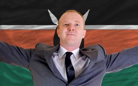 joyful investor spreading arms after good business investment in kenya, in front of flag photo