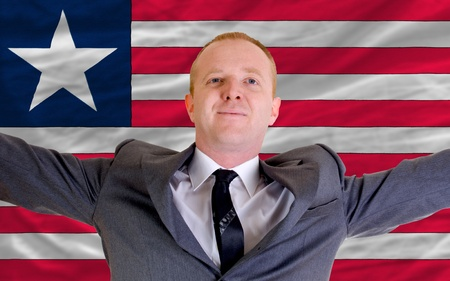joyful investor spreading arms after good business investment in liberia, in front of flag photo