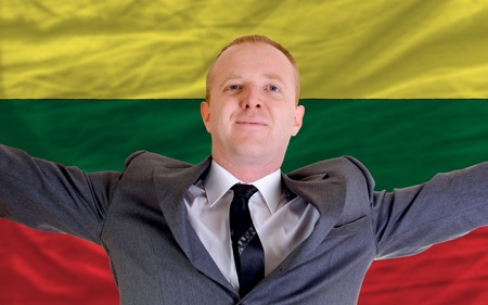 joyful investor spreading arms after good business investment in lithuania, in front of flag photo