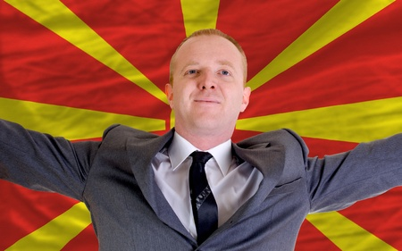 spreading arms: joyful investor spreading arms after good business investment in macedonia, in front of flag Stock Photo