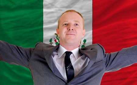 joyful investor spreading arms after good business investment in mexico, in front of flag