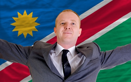 spreading arms: joyful investor spreading arms after good business investment in namibia, in front of flag Stock Photo