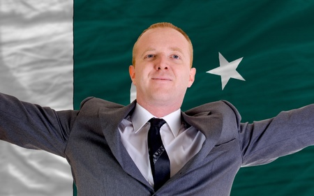spreading arms: joyful investor spreading arms after good business investment in pakistan, in front of flag