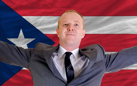 puertorico: joyful investor spreading arms after good business investment in puertorico, in front of flag