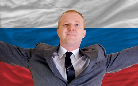 spreading arms: joyful investor spreading arms after good business investment in russia, in front of flag