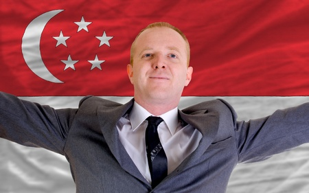 singaporean flag: joyful investor spreading arms after good business investment in singapore, in front of flag
