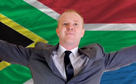spreading arms: joyful investor spreading arms after good business investment in south africa, in front of flag
