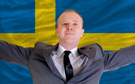 spreading arms: joyful investor spreading arms after good business investment in sweden, in front of flag Stock Photo