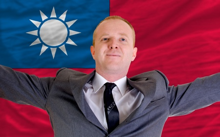 spreading arms: joyful investor spreading arms after good business investment in taiwan, in front of flag