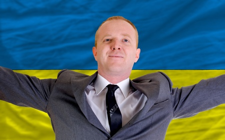 spreading arms: joyful investor spreading arms after good business investment in ukraine, in front of flag
