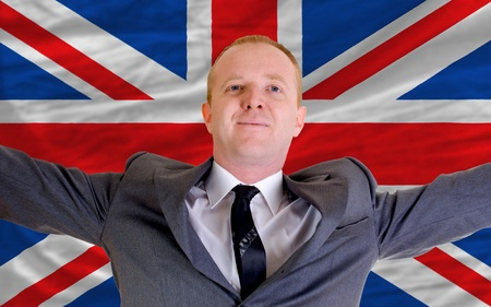 spreading arms: joyful investor spreading arms after good business investment in united kingdom, in front of flag