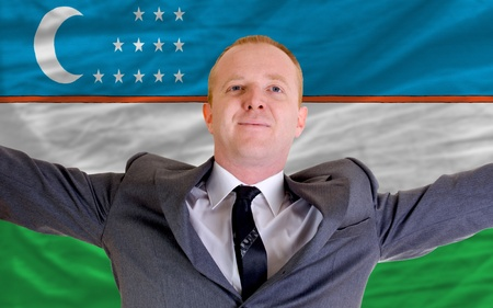 joyful investor spreading arms after good business investment in uzbekistan, in front of flag photo