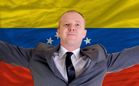spreading arms: joyful investor spreading arms after good business investment in venezuela, in front of flag