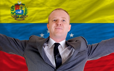 joyful investor spreading arms after good business investment in venezuela, in front of flag photo