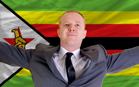 spreading arms: joyful investor spreading arms after good business investment in zimbabwe, in front of flag Stock Photo
