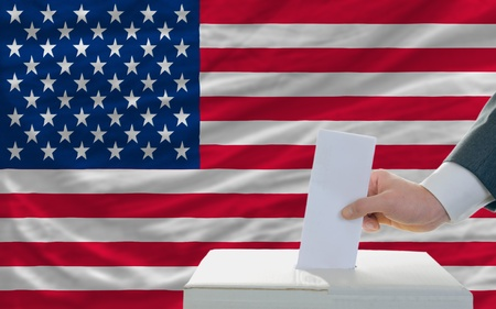 ballot paper: man putting ballot in a box during elections in america in front of flag