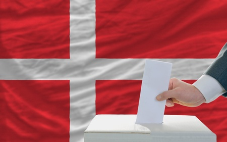 man putting ballot in a box during elections in denmark in fornt of flag photo