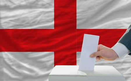 man putting ballot in a box during elections in england in fornt of flag photo
