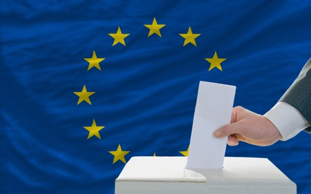 man putting ballot in a box during elections in europe in fornt of flag
