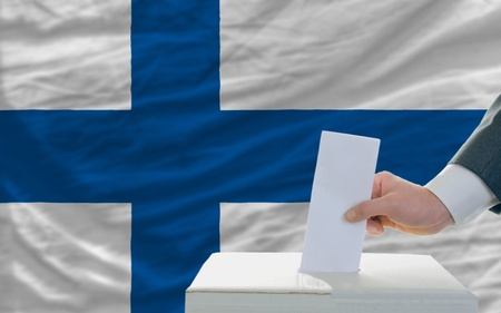 man putting ballot in a box during elections in finland in fornt of flag photo