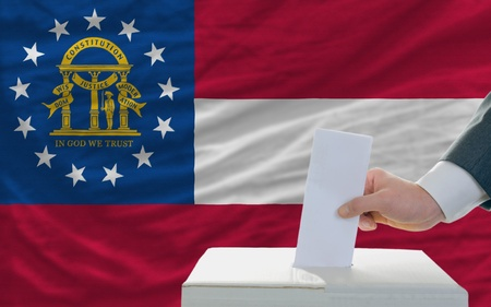 man putting ballot in a box during elections in georgia in fornt of flag photo