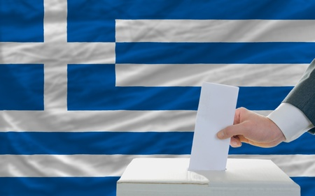 man putting ballot in a box during elections in greece in fornt of flag