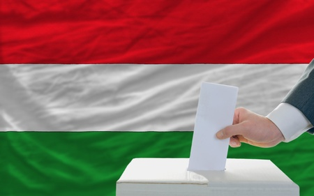 parliamentary: man putting ballot in a box during elections in hungary in fornt of flag