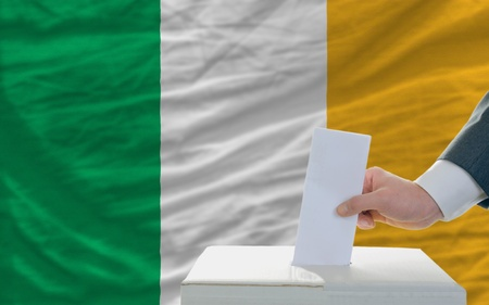man putting ballot in a box during elections in ireland in fornt of flag photo