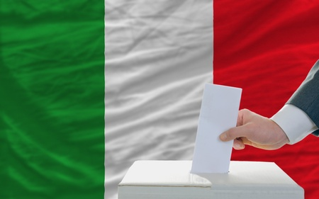 man putting ballot in a box during elections in italy in fornt of flag