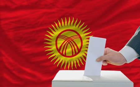 man putting ballot in a box during elections in kyrghyzstan in fornt of flag photo