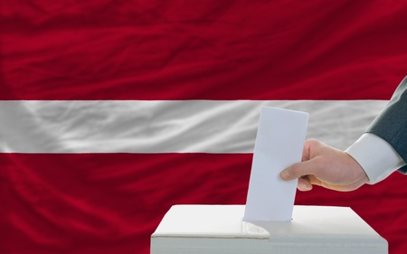 man putting ballot in a box during elections in latvia in front of flag photo
