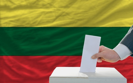 parliamentary: man putting ballot in a box during elections in lithuania in front of flag Stock Photo