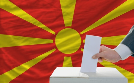man putting ballot in a box during elections in macedonia in front of flag photo