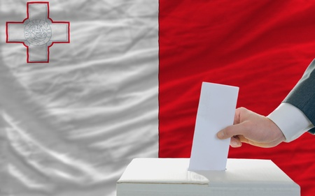 man putting ballot in a box during elections in malta in front of flag photo