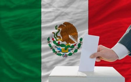 democracia: hombre poniendo voto en una urna durante las elecciones en M�xico delante de la bandera