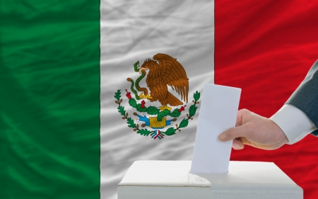 vote: man putting ballot in a box during elections in mexico in front of flag